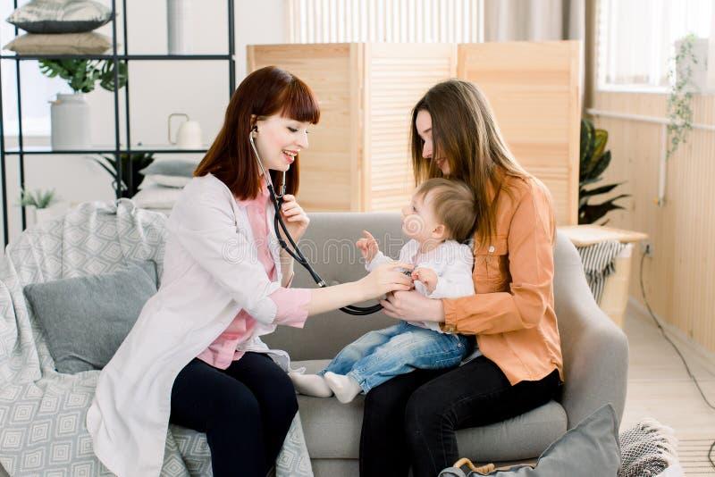 使用听诊器的一位白种人女性儿科医生的画象审查女婴在母亲手 库存照片