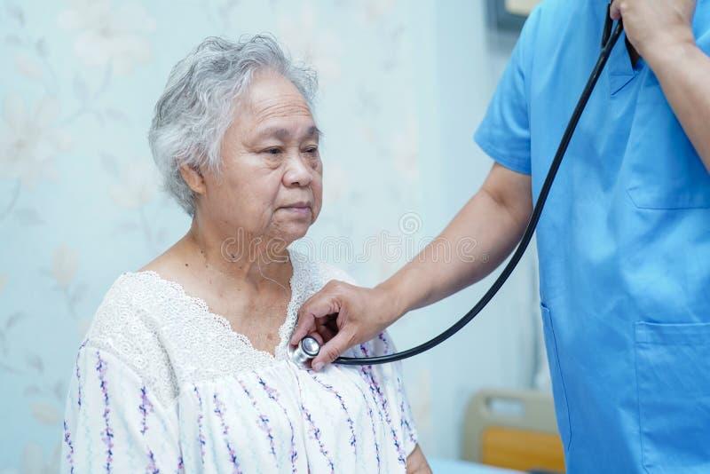 使用听诊器的医生对检查患者下来坐一张床在医院病房里:健康强医疗 免版税库存照片