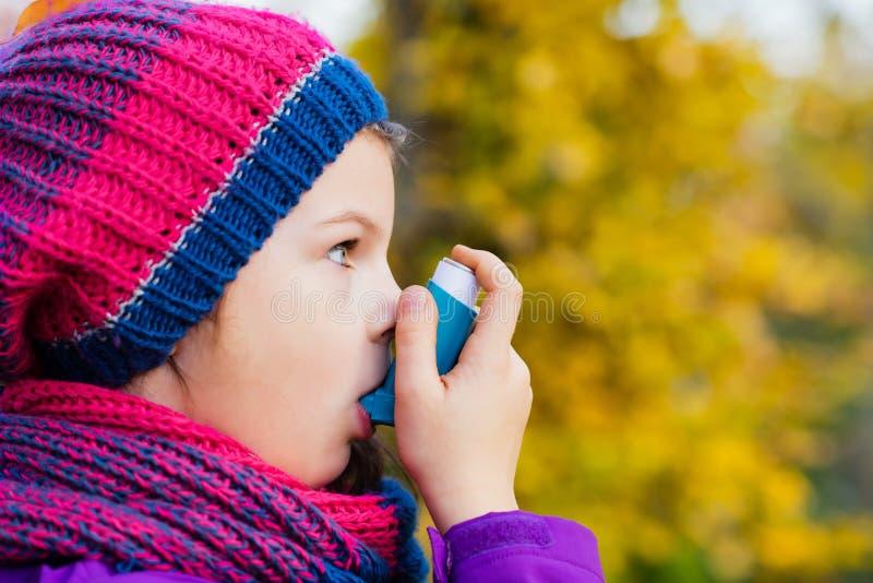 使用吸入器的女孩在一秋天天 免版税库存图片