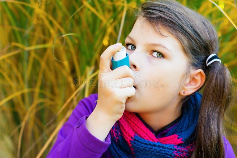 使用吸入器的女孩在一秋天天 库存照片