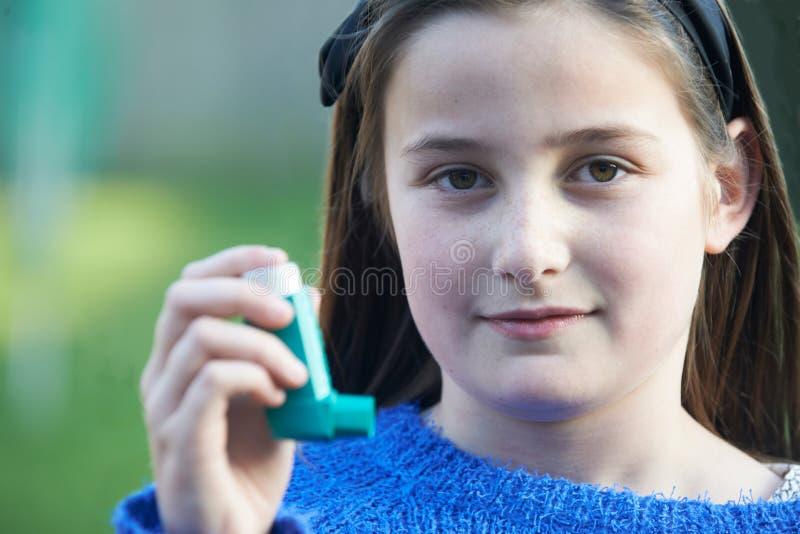 使用吸入器的女孩对待哮喘病发作 免版税库存图片