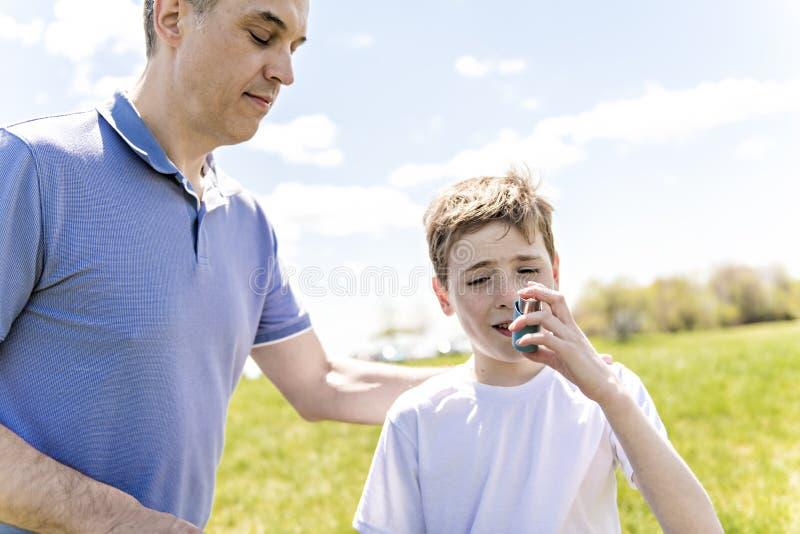 使用吸入器的孩子为哮喘外部在有他的父亲的一个公园 免版税库存图片