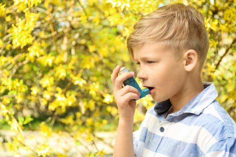 使用吸入器的小男孩在开花的树附近 r 免版税图库摄影