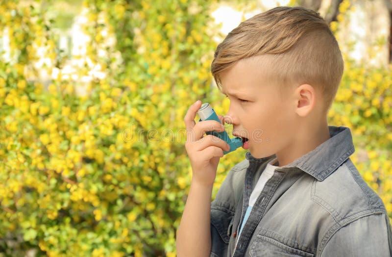 使用吸入器的小男孩在开花的树附近 r 免版税库存图片