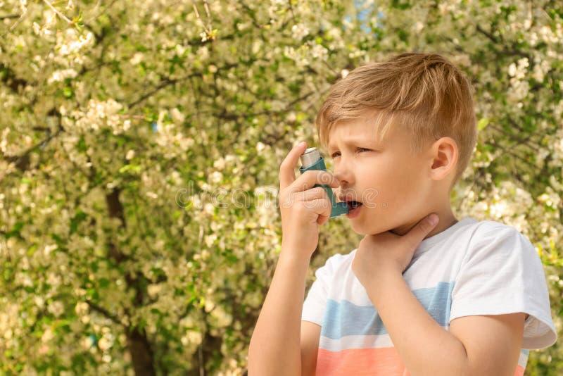 使用吸入器的小男孩在开花的树附近 r 库存照片