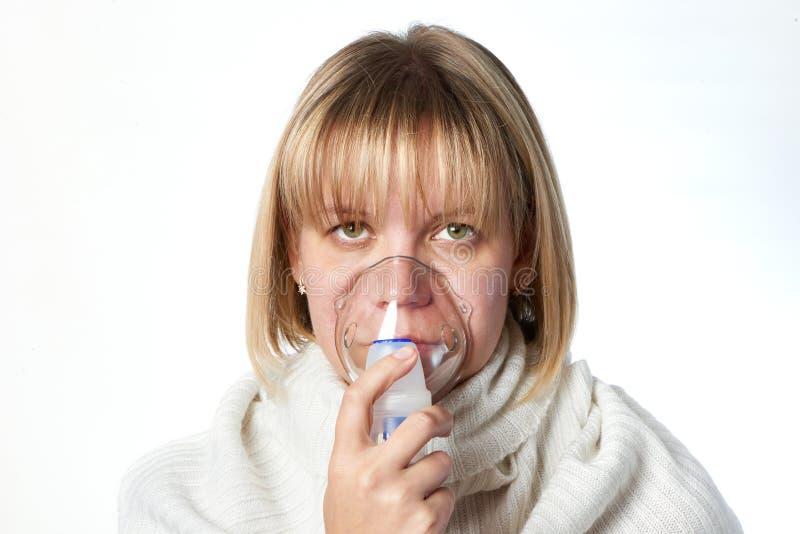 使用吸入器面具的病的咳嗽妇女被隔绝 免版税图库摄影