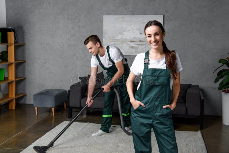 使用吸尘器和微笑的年轻清洗的公司工作者 免版税图库摄影
