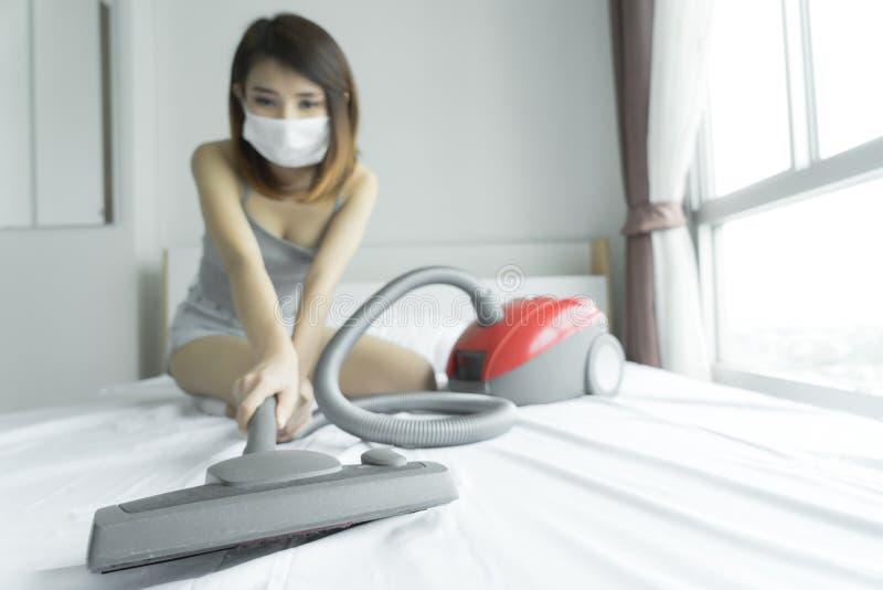 使用吸尘器的妇女,当清洗白色床在homeBeau时 图库摄影