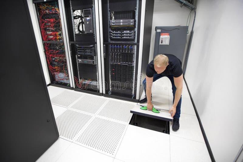 使用吸杯的IT工程师举的地垫在Datacenter 图库摄影