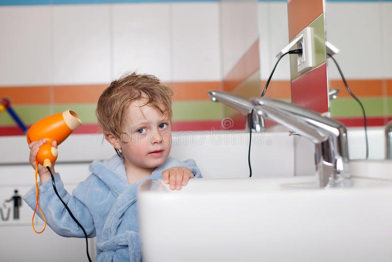 使用吹风器的男孩在卫生间 免版税库存照片