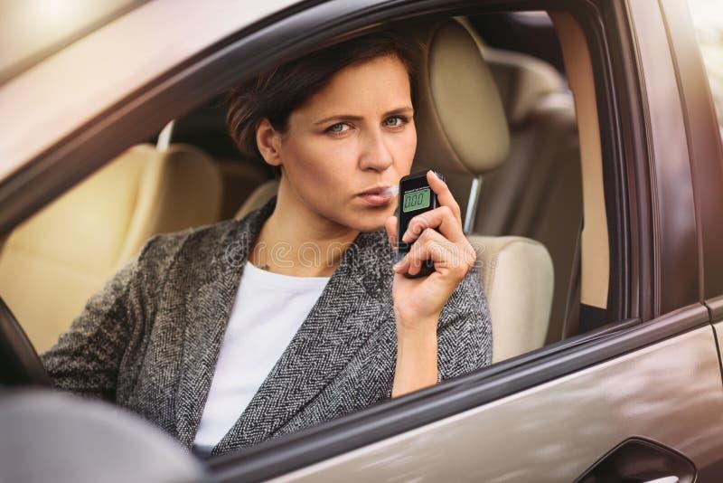 使用呼吸酒精分析仪的妇女在汽车 图库摄影