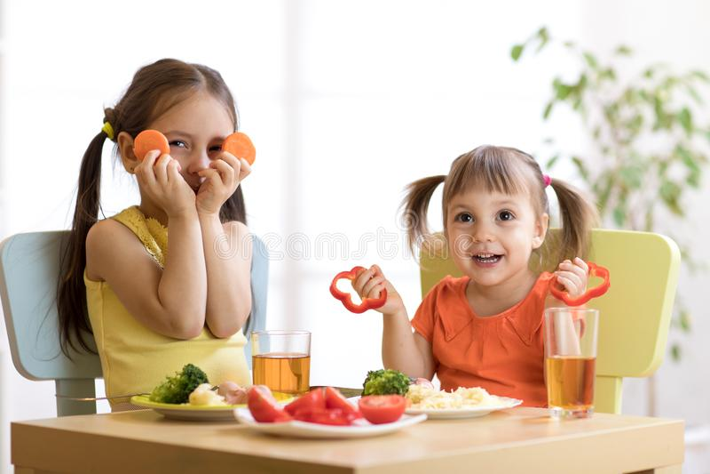使用和吃在幼儿园的滑稽的孩子 库存照片