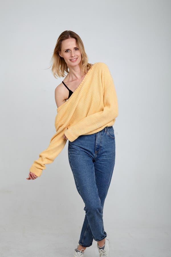 使用和微笑 在全长的一张画象一个美丽的金发碧眼的女人,穿戴在时髦的衣裳 在白色前面的姿势 图库摄影