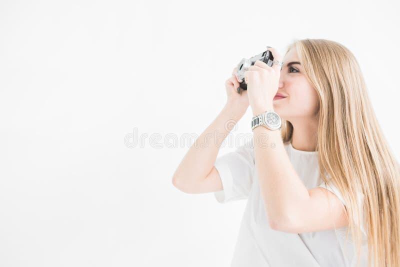 使用和拍在一台老葡萄酒照相机的一个年轻时髦的白肤金发的女孩的画象照片在白色背景 免版税库存照片