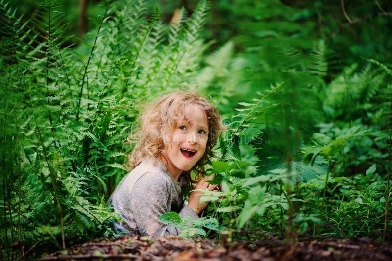 使用和掩藏在狂放的蕨的愉快的儿童女孩在夏天森林里 库存图片
