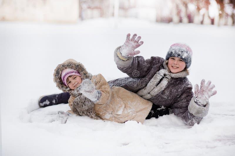 使用和笑在多雪的冬天公园的滑稽的孩子 库存图片