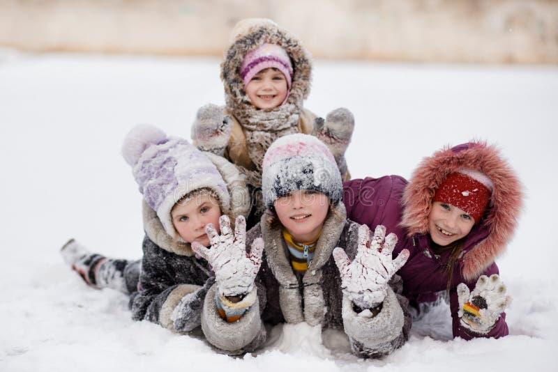 使用和笑在多雪的冬天公园的滑稽的孩子 免版税图库摄影