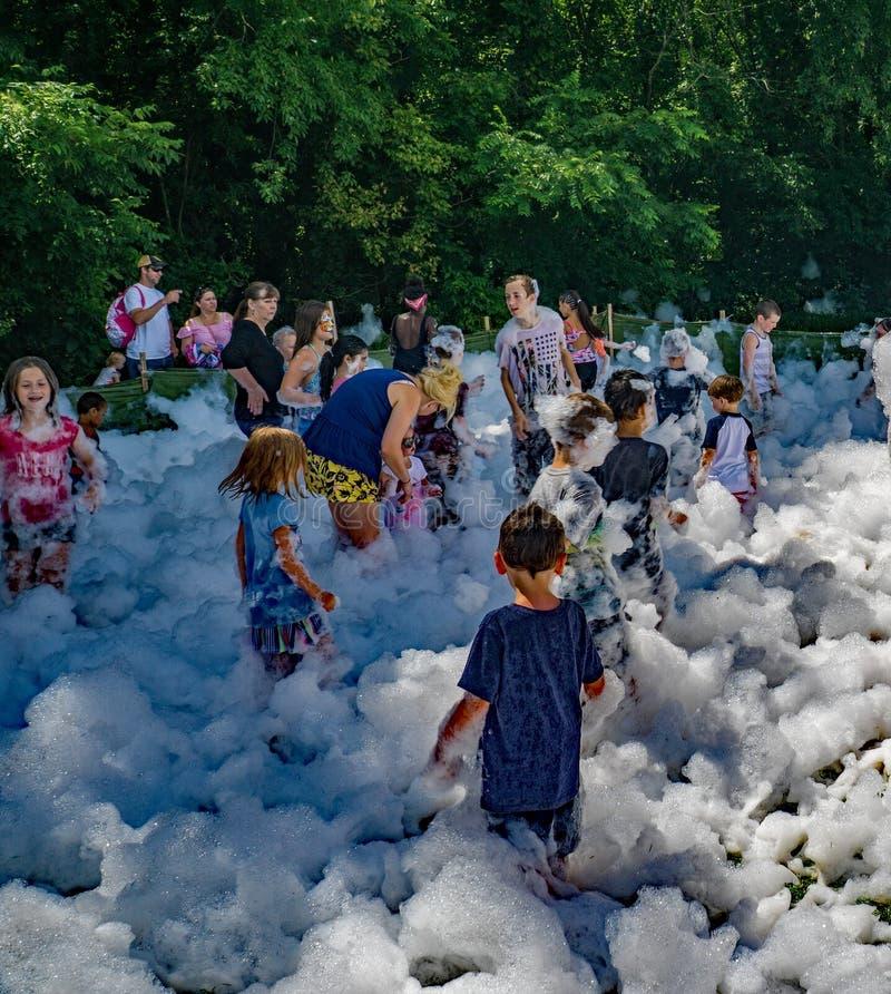 使用和笑在Firemen's泡沫的孩子 免版税库存图片