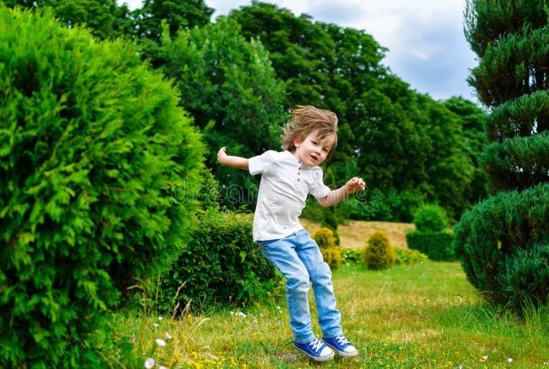 使用和跳跃在公园的愉快的小男孩 免版税库存图片