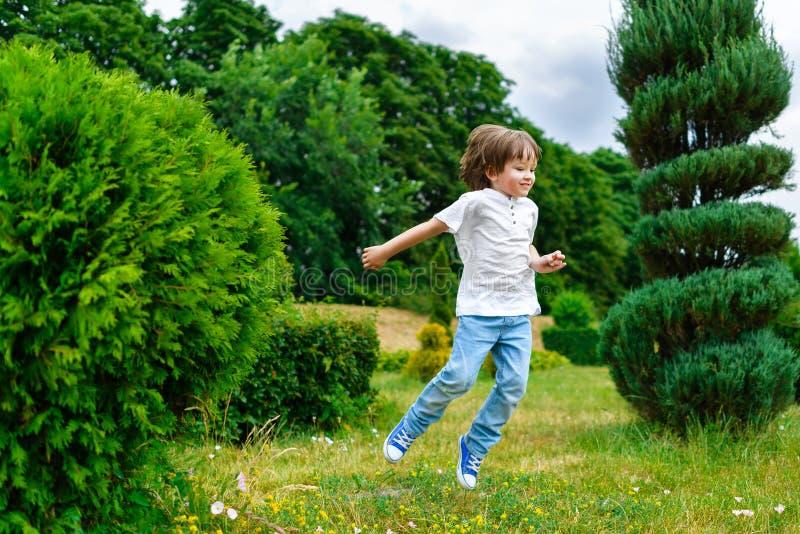 使用和跳跃在公园的愉快的小男孩 图库摄影