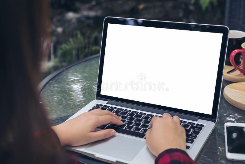 使用和键入在有空白的白色屏幕、巧妙的电话和咖啡杯的膝上型计算机的女商人在玻璃桌上 免版税库存图片