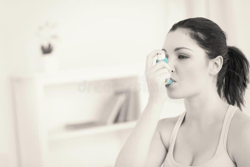 使用哮喘吸入器的妇女在客厅 免版税图库摄影