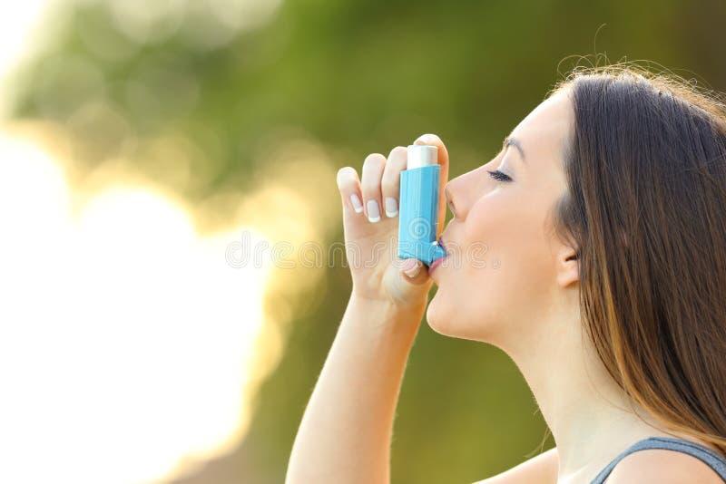 使用哮喘吸入器的妇女户外 免版税库存照片