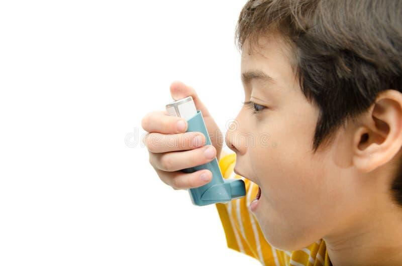 使用哮喘吸入器的小男孩为呼吸 库存照片