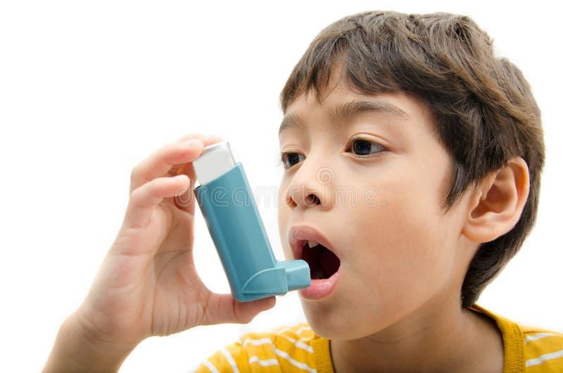 使用哮喘吸入器的小男孩为呼吸 免版税图库摄影