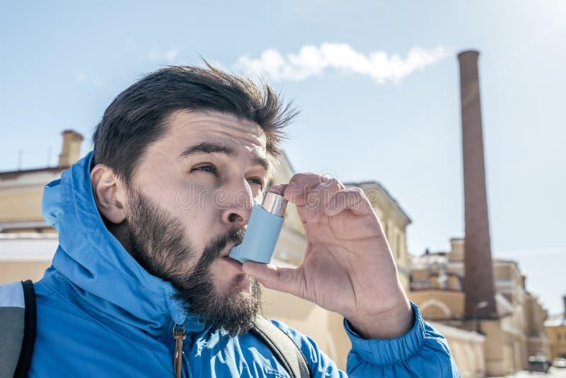 使用哮喘吸入器的年轻人画象室外 库存照片