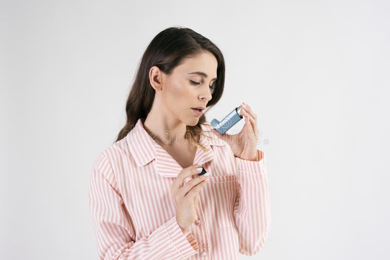 使用哮喘吸入器的气喘妇女在哮喘病发作期间 库存照片