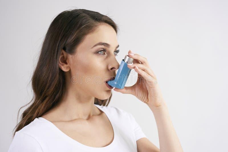 使用哮喘吸入器的气喘妇女在哮喘病发作期间 免版税库存照片