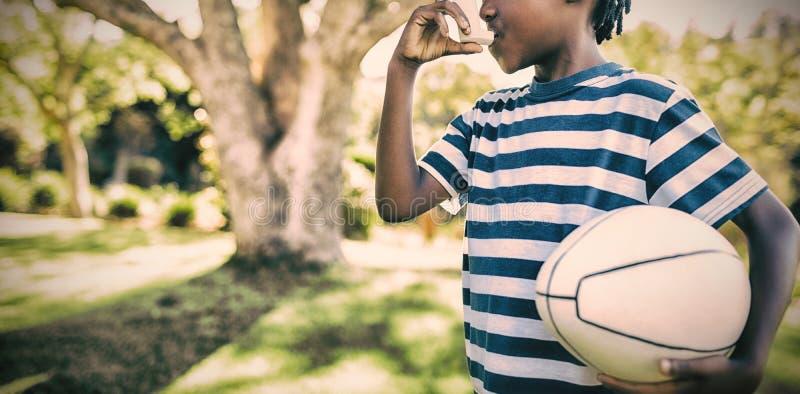 使用哮喘吸入器的男孩在公园 免版税图库摄影