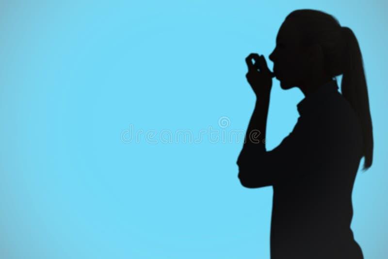 使用哮喘吸入器的美丽的金发碧眼的女人的综合图象 库存图片