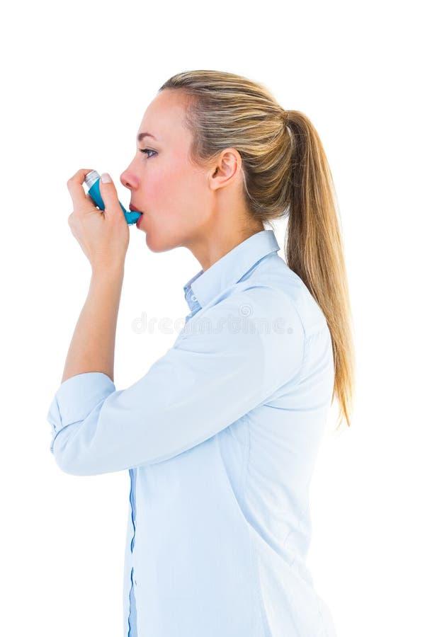 使用哮喘吸入器的美丽的金发碧眼的女人 库存照片