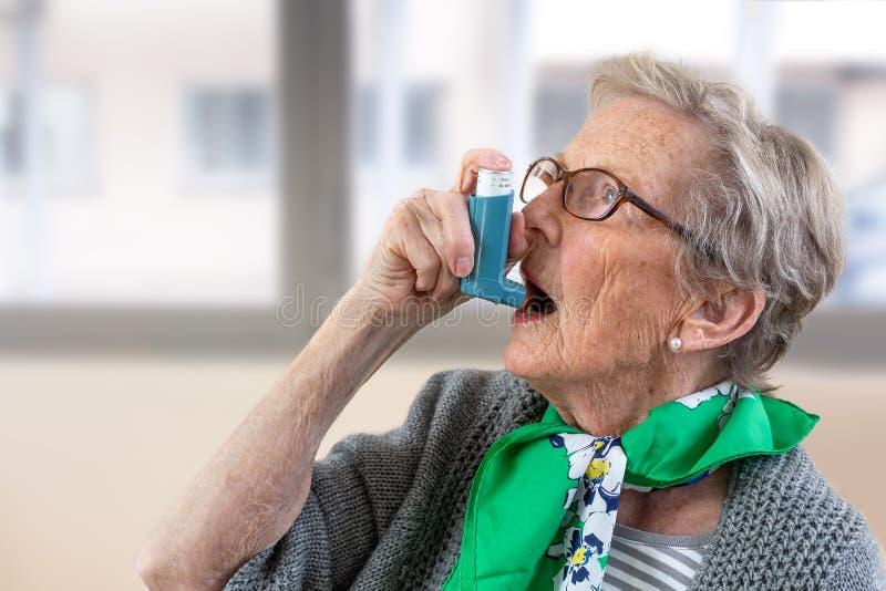 使用哮喘吸入器的资深妇女特写镜头  库存照片