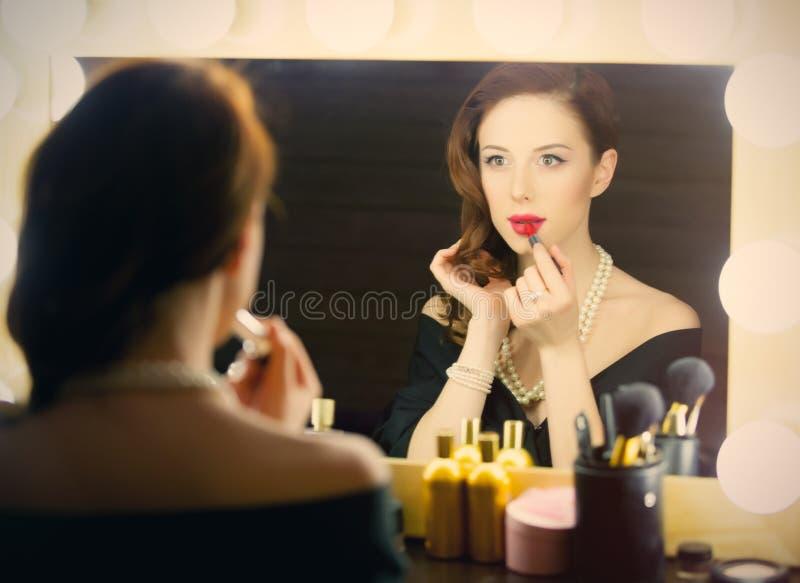 使用唇膏的美丽的少妇画象和看 库存图片