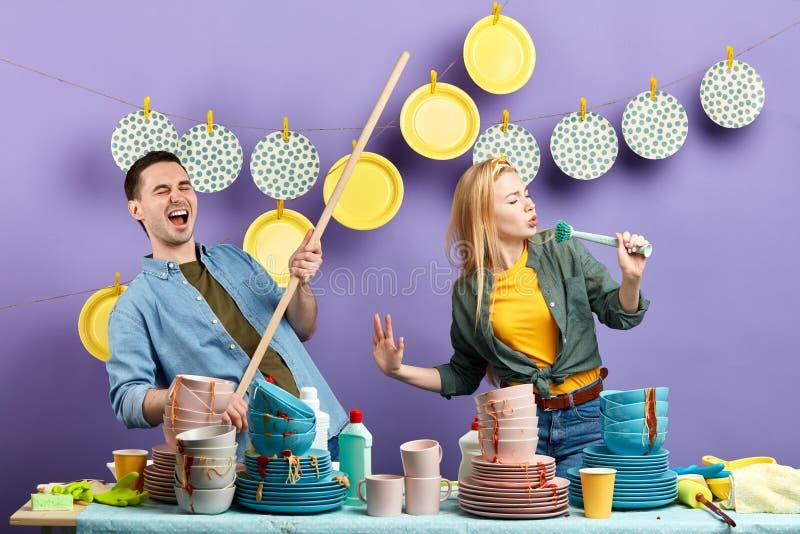 使用唱歌的刷子和的笤帚的年轻情感夫妇跳舞和 免版税库存图片