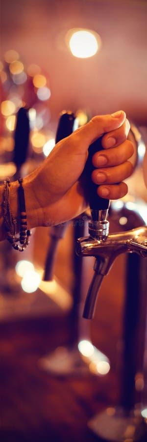 使用啤酒轻拍的侍酒者手在客栈 库存例证