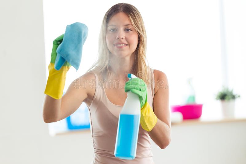 使用喷粉器和浪花的美丽的年轻女人和微笑,当在家时清洗窗口 免版税库存图片