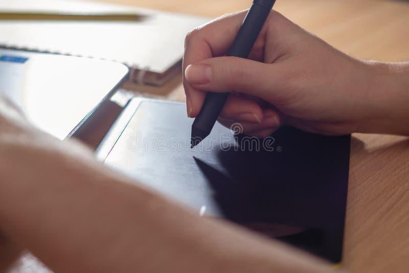 使用图形输入板的以图例解释者 妇女的使用膝上型计算机和画的片剂的retoucher的手 图库摄影
