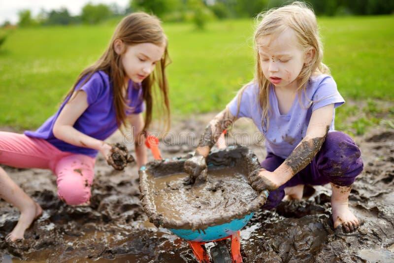 使用在一个大湿泥浆坑的两个滑稽的小女孩在晴朗的夏日 得到的孩子肮脏,当开掘在泥泞的土壤时 图库摄影