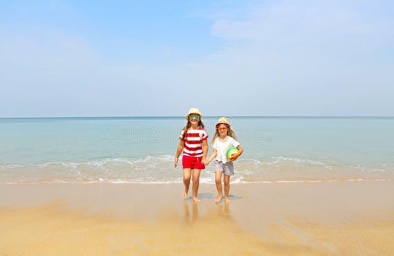 使用在一个美丽的海滩的沙子的愉快的姐妹 免版税图库摄影