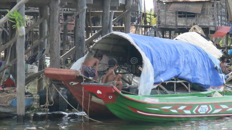 使用在一条残破的小船的孩子在浮动村庄在Tonle Sap湖柬埔寨 图库摄影