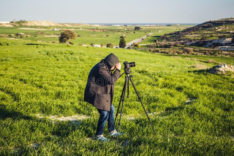 使用在三脚架的摄影师或旅行家一台专业DSLR照相机在自然为背景 免版税图库摄影