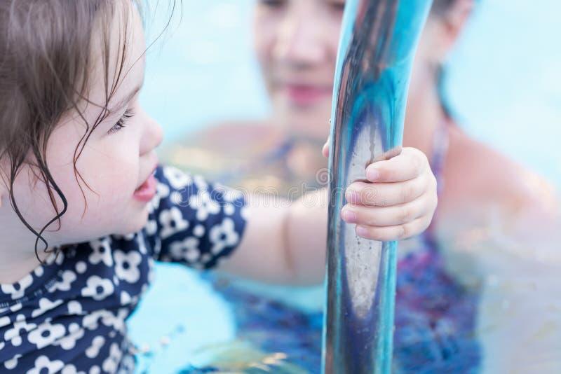 使用在与她的母亲的游泳池的愉快的小女孩 免版税库存图片