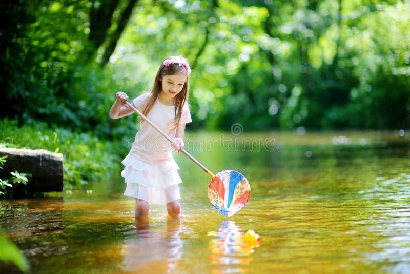 使用在与她的瓢网的河传染性的橡胶鸭子的逗人喜爱的小女孩 免版税库存图片