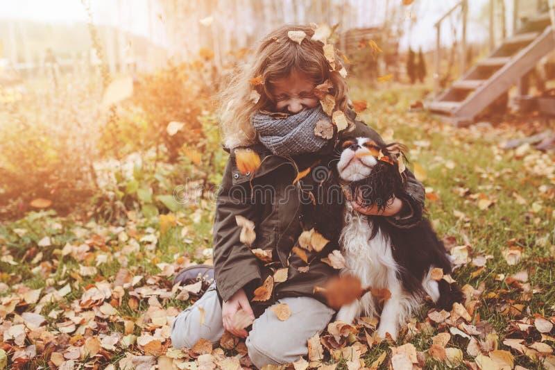 使用在与她的骑士国王查尔斯狗狗的秋天的愉快的儿童女孩 免版税库存图片
