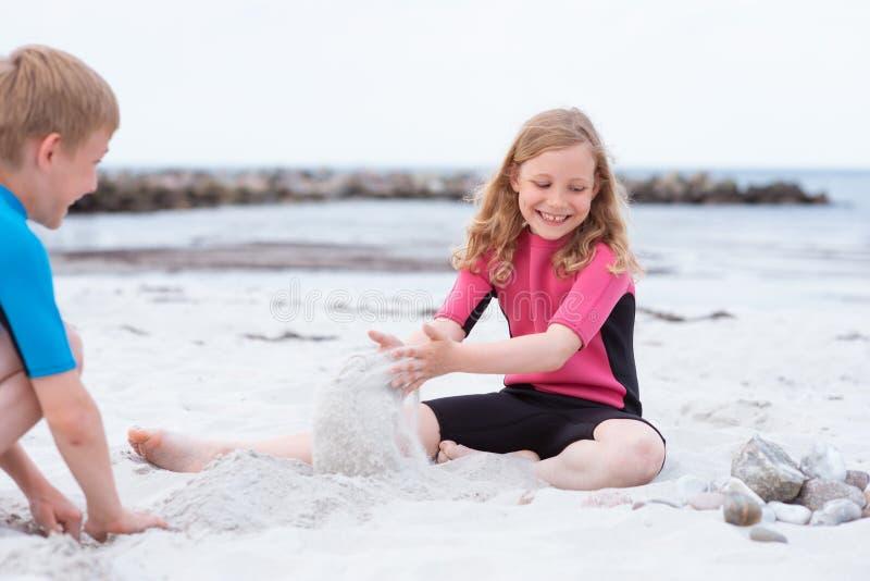 使用在与沙子的海滩的氯丁胶泳装的两个孩子 库存照片