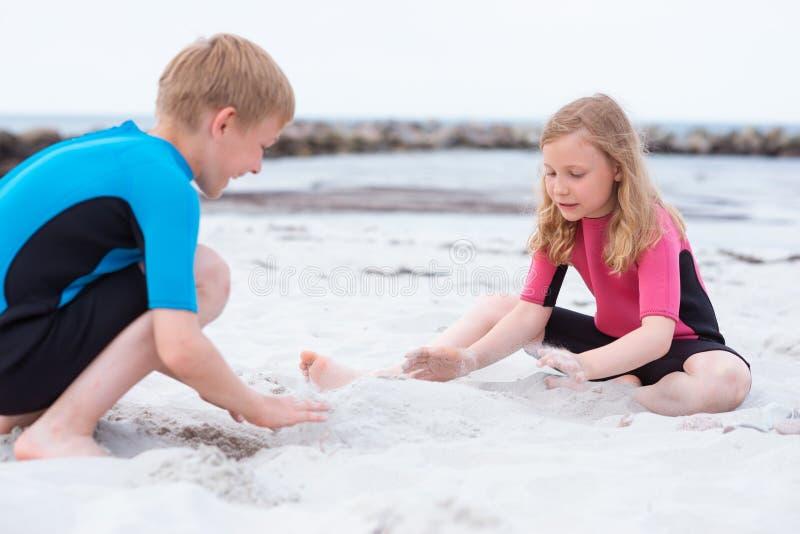 使用在与沙子的海滩的氯丁胶泳装的两个孩子 免版税库存图片